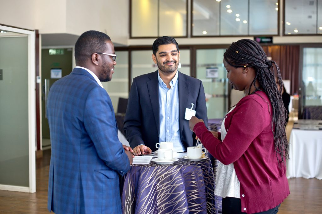 Three Oxford Policy Fellows talking while drinking coffee