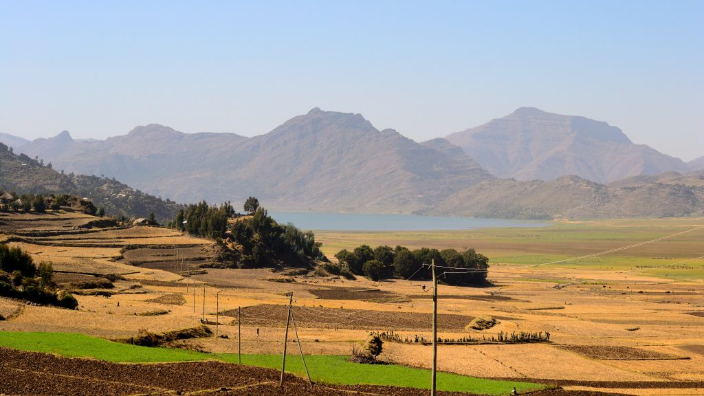 A mountainous Ethiopian countryside, traversed by power lines.
